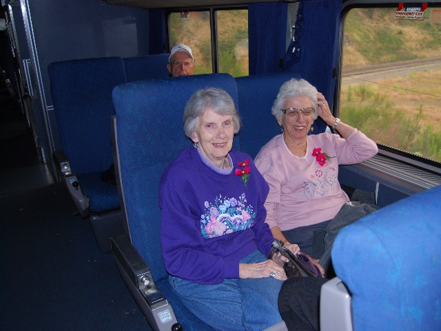 Two Ladies in Train Seats Smiling
